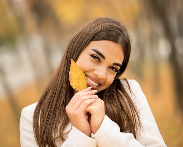 Kaukasische aantrekkelijke vrouw die lacht en een gevallen blad vasthoudt in de herfst