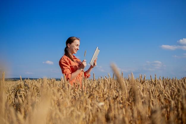 Kaukasische agronoom die het gebied van granen controleert en gegevens vanaf de tablet naar de cloud verzendt. slimme landbouw en digitaal landbouwconcept. succesvolle biologische voedselproductie en -teelt.
