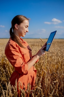 Kaukasische agronoom die het gebied van granen controleert en gegevens vanaf de tablet naar de cloud verzendt