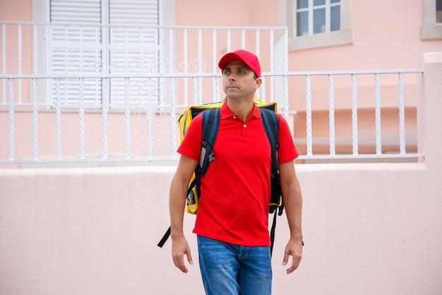 Kaukasische arbeider die gele thermische rugzak draagt. koerier of bezorger van middelbare leeftijd in rood uniform rondkijken, staande en bestelling afleveren. bezorgservice en online winkelconcept