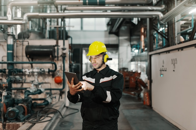 Kaukasische arbeider in zware industrieinstallatie met helm en in eenvormige gebruikende tablet voor het werk.