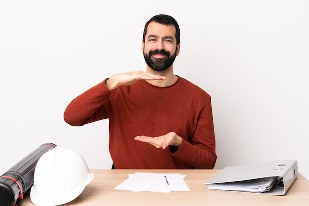 Kaukasische architectenmens met baard in een lijst die copyspace denkbeeldig op de palm houdt om een advertentie in te voegen.
