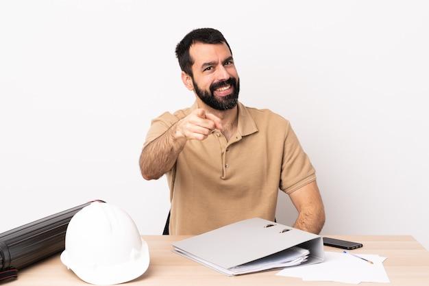 Kaukasische architectenmens met baard in een lijst die met gelukkige uitdrukking naar voren wijst.
