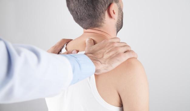 Kaukasische arts die de nek van de mens masseert.