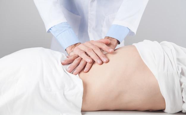 Kaukasische arts die de wervelkolom van de patiënt masseert