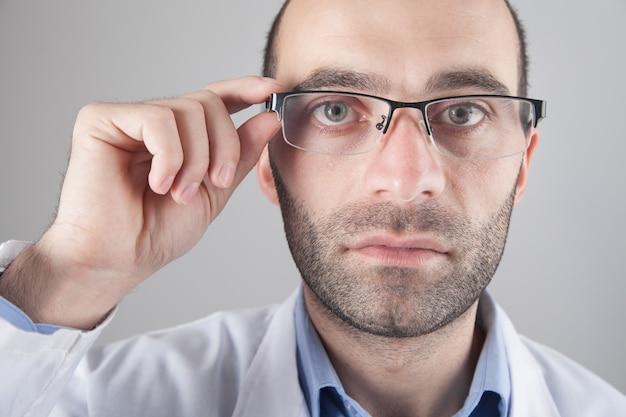 Kaukasische arts die een bril draagt die naar de camera kijkt.