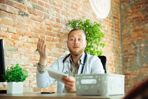 Kaukasische arts die voor patiënt raadpleegt, die in kabinet werkt