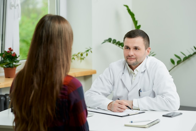 Kaukasische arts in witte laboratoriumjaszitting bij bureau en het luisteren aan patiënt