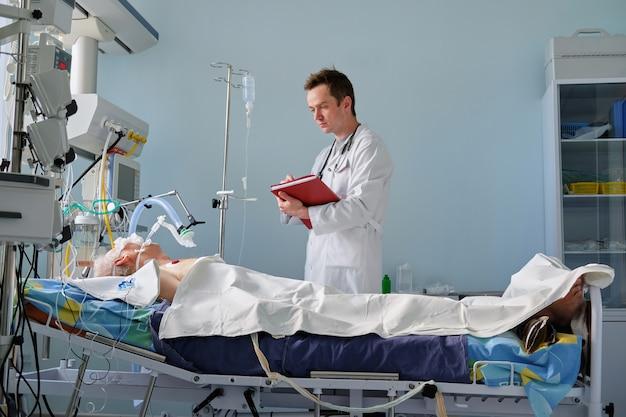 Kaukasische arts voor intensieve zorg onderzoekt geïntubeerde kritische houding patiënt schrijft aantekeningen bij casusverslag op intensive care-afdeling