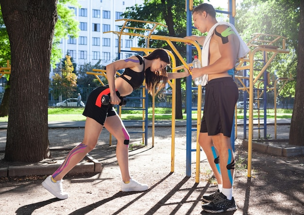 Kaukasische atleten koppelen met kinesiologie elastische taping op lichamen