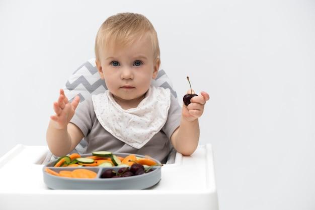 Kaukasische baby van ongeveer 1 jaar oud die verse groenten eet in de kinderstoel op een witte achtergrond zelfvoeding voor kinderen babyled-speenidee gezonde voeding van vast voedsel voor zuigelingenkopieer ruimte voor tekst