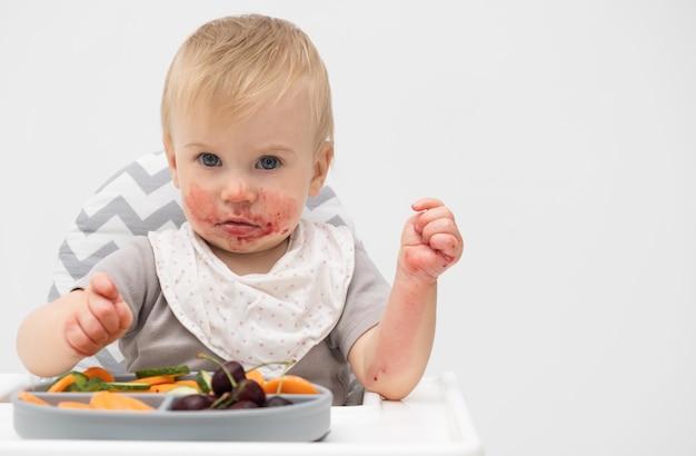 Kaukasische baby van ongeveer 1 jaar oud die verse groenten eet in de kinderstoel op witte achtergrond zelfvoeding voor kinderen babyled speenidee gezonde voeding van vast voedsel voor zuigelingen ruimte voor tekst kopiëren