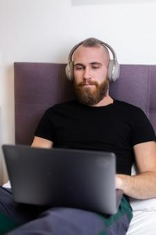 Kaukasische bebaarde man in koptelefoon in slaapkamer op bed bezig met laptop vanuit huis, typen, denken.