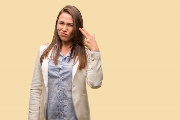 Kaukasische bedrijfs jonge vrouw die een zelfmoordgebaar doet