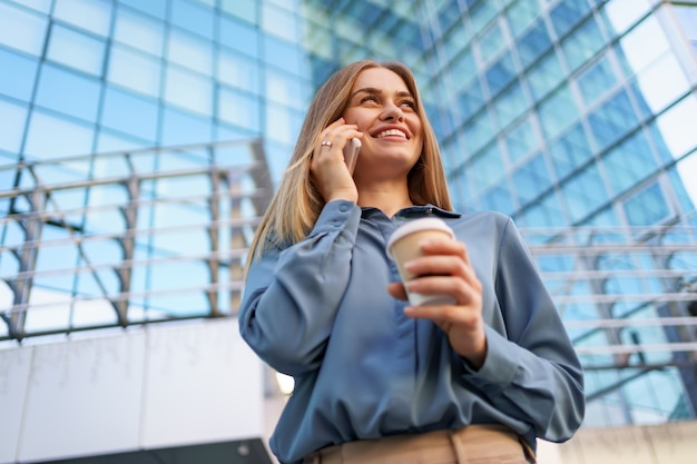 Kaukasische bedrijfsvrouw die telefonisch spreekt die koffie houdt om te gaan. een succesvolle europese vrouw, praten aan de telefoon, staande op een modern kantoorgebouw