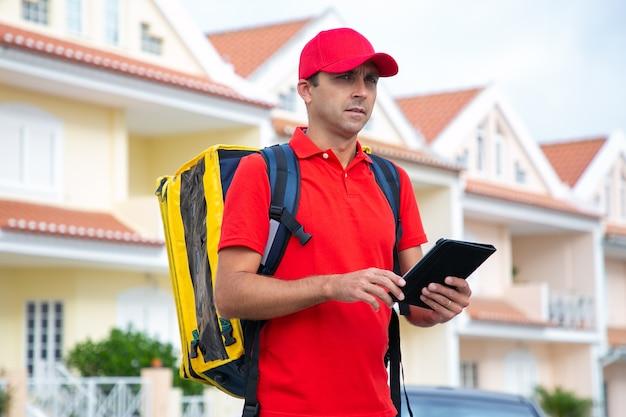 Kaukasische bezorger die adres zoekt en tablet vasthoudt. nadenkende koerier die de bestelling aflevert in een gele thermorugzak.