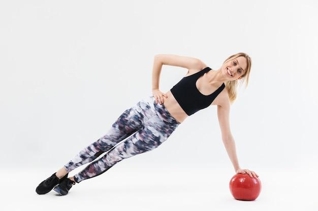 Kaukasische blonde vrouw 20s gekleed in sportkleding uit te werken en oefeningen te doen met fitnessbal tijdens aerobics geïsoleerd over witte muur