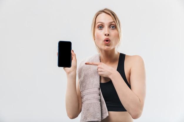Kaukasische blonde vrouw gekleed in sportkleding met handdoek over nek met smartphone tijdens training in sportschool geïsoleerd over witte muur