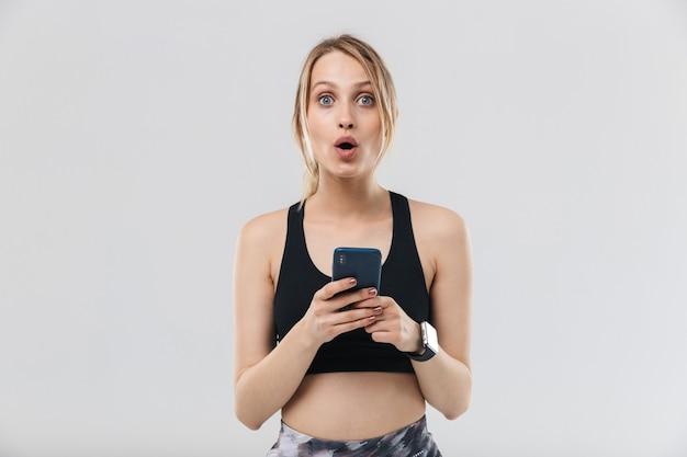 Kaukasische blonde vrouw gekleed in sportkleding met smartphone tijdens training in sportschool geïsoleerd over witte muur