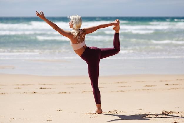 Kaukasische blonde vrouw het praktizeren yoga in het strand