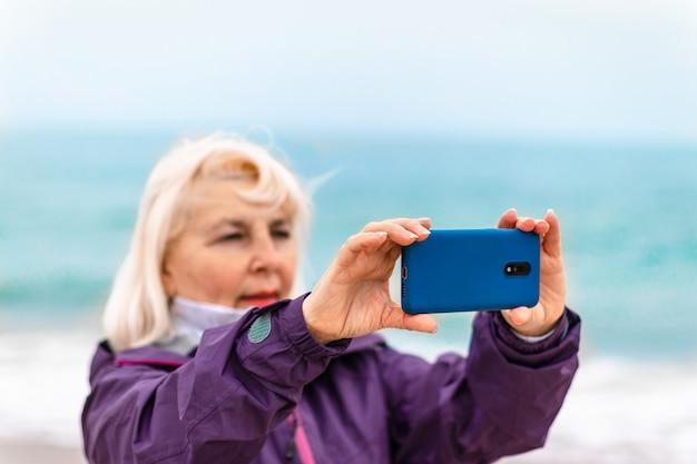 Kaukasische blonde vrouwenreiziger die op strand loopt en telefonisch foto's neemt of video opneemt