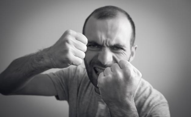 Kaukasische boze en agressieve man die met vuisten dreigt.
