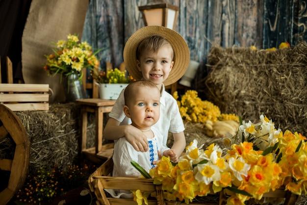Kaukasische broer en zus zitten in een houten kar met bloemen en knuffelen op het oppervlak van een hooiberg. rustieke stijl.