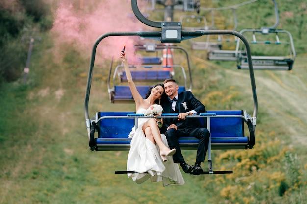 Kaukasische bruidspaar rijden kabelbaan met kleurrijke rook in hun handen.