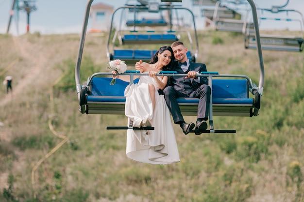 Kaukasische bruidspaar rijden kabelbaan.