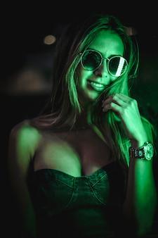 Kaukasische brunette in een zwarte jurk verlicht door groene led licht weerspiegeld in zwarte kristallen. stedelijke nachtfotografie. close-up portret met zonnebril