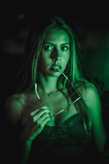 Kaukasische brunette in een zwarte jurk verlicht door groene led licht weerspiegeld in zwarte kristallen. stedelijke nachtfotografie. vrouw bijten zonnebril