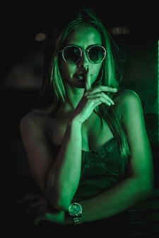 Kaukasische brunette in een zwarte jurk verlicht door groene led licht weerspiegeld in zwarte kristallen. stedelijke nachtfotografie. vrouw met zonnebril en stil zeggen