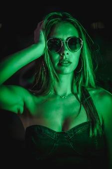 Kaukasische brunette in een zwarte jurk verlicht door groene led licht weerspiegeld in zwarte kristallen. stedelijke nachtfotografie. vrouw met zonnebril
