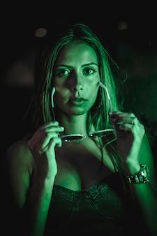 Kaukasische brunette in een zwarte jurk verlicht door groene led licht weerspiegeld in zwarte kristallen. stedelijke nachtfotografie. vrouw zonnebril opstijgen