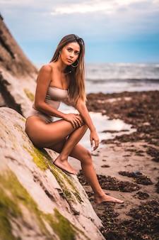 Kaukasische brunette met een bruin zwempak aan zee