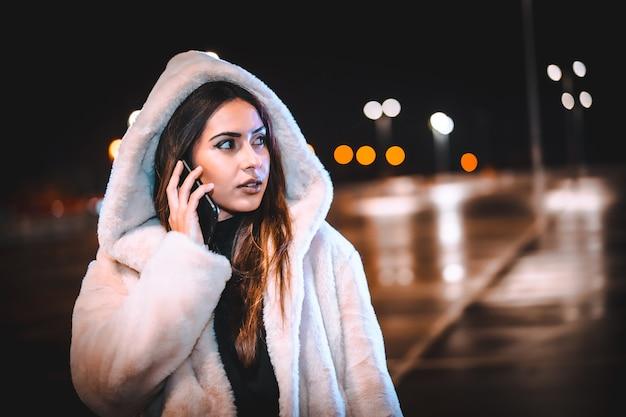Kaukasische brunette praten aan de telefoon in een roze wollen jas in een lege parkeerplaats. nachtelijke stedelijke sessie in de stad