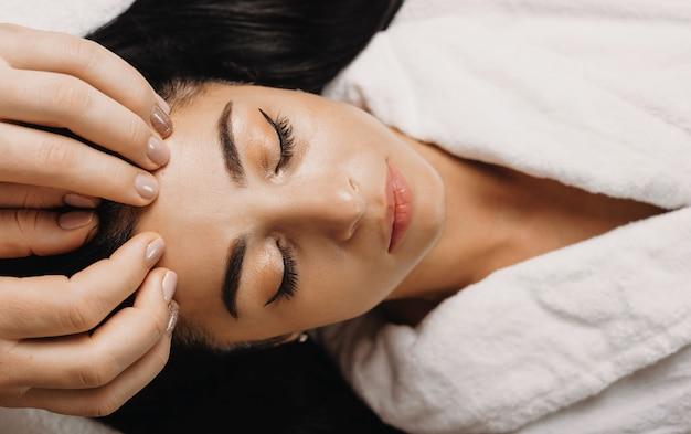 Kaukasische brunette vrouw wacht terwijl het hebben van een gezichtsmassagesessie in een kuuroordsalon