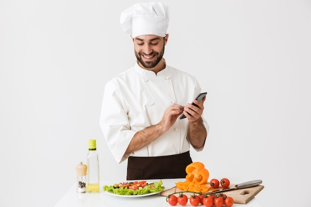 Kaukasische chef-kok man in uniform glimlachend en smartphone vast te houden tijdens het koken van groentesalade geïsoleerd over witte muur