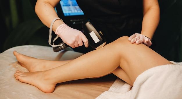 Kaukasische cliënt met een been epilatie sessie in een professionele spa salon