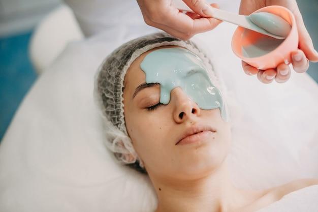 Kaukasische dermatoloog brengt een blauw masker aan op het gezicht van de cliënt tijdens spa-procedures