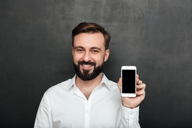 Kaukasische donkerbruine mens die smartphone op camera tonen die of gadget over grafietexemplaarruimte adverteren adverteren