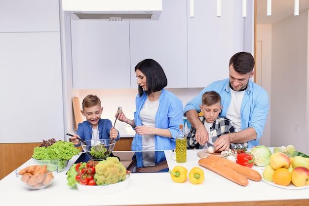 Kaukasische en gelukkige familie met twee zonen die gezond vegetarisch ontbijt met en groenten op keuken voorbereiden