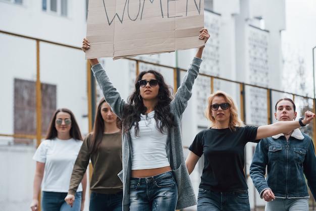 Kaukasische etniciteit. een groep feministische vrouwen protesteert buitenshuis voor hun rechten