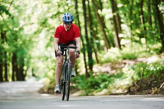 Kaukasische etniciteit. fietser op een fiets is op de asfaltweg in het bos op zonnige dag