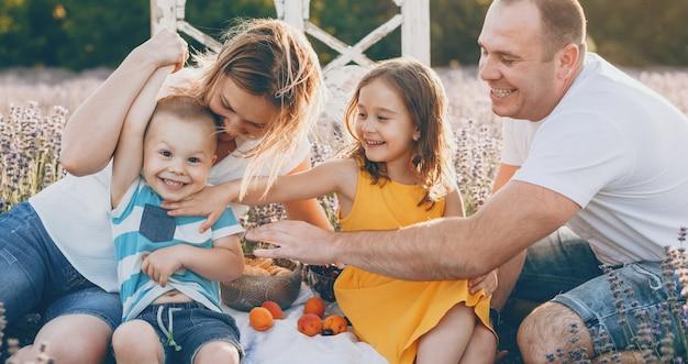 Kaukasische familie die een picknick heeft dichtbij een lavendelgebied die gelukkig samen stelt