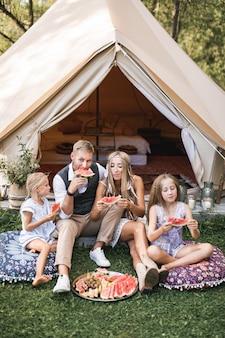 Kaukasische familie die een picknick heeft en in bos kampeert, die voor grote wigwamtent zit