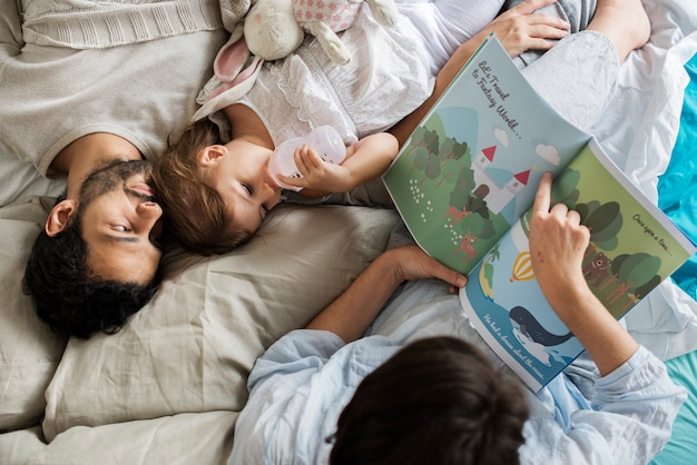 Kaukasische familie die sprookjes lezen aan zij dochter met geluk