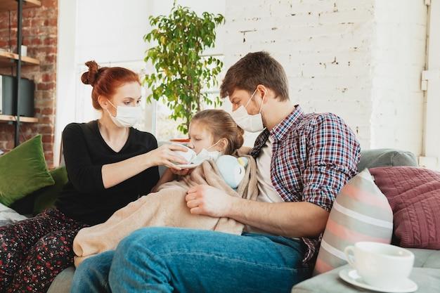 Kaukasische familie in gezichtsmaskers en handschoenen thuis geïsoleerd met coronavirus luchtwegsymptomen zoals koorts, hoofdpijn, hoesten in milde toestand. gezondheidszorg, medicijnen, quarantaine, behandelingsconcept.