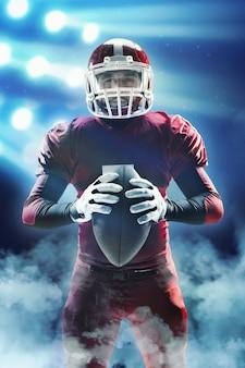 Kaukasische fitness man als american football speler met een bal op de achtergrond van het stadion