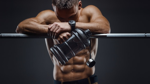 Kaukasische fitness man drinkwater na training in de sportschool.
